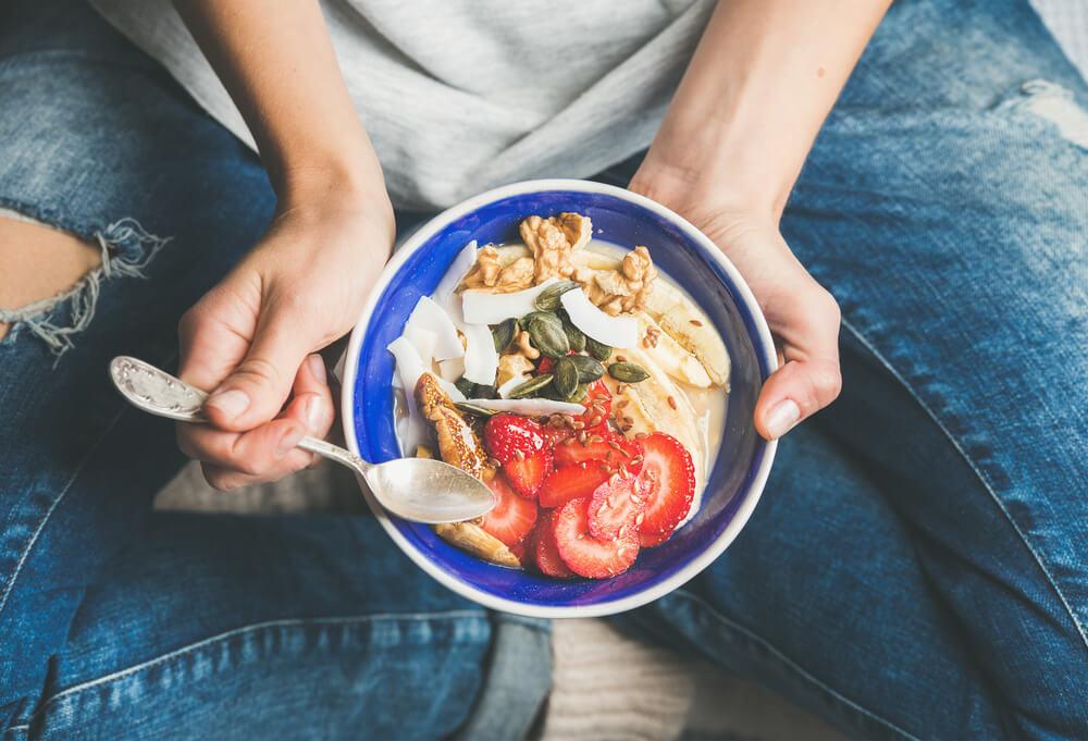 אישה מחזיקה צלחת עם ארוחה בריאה בפנים